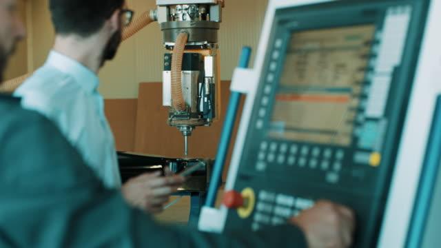 zwei ingenieure ist die programmierung einer cnc-fräsmaschine - fließbandfertigung stock-videos und b-roll-filmmaterial