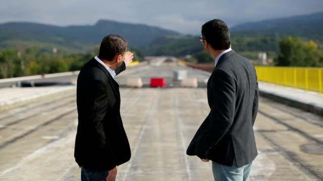 vidéos et rushes de deux ingénieurs planification autoroute site de construction - technicien