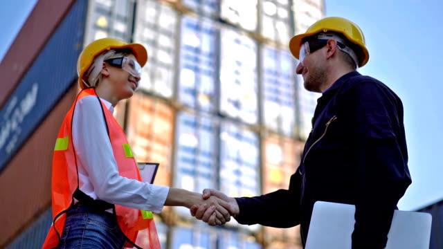 vidéos et rushes de deux ingénieurs serrant la main au dock d'expédition - débardeur