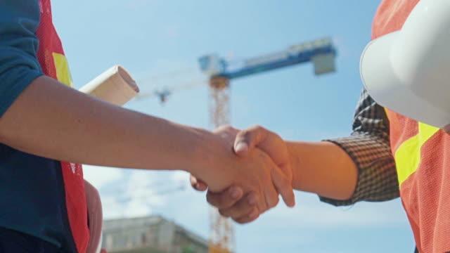 vidéos et rushes de deux ingénieurs se serrant la main sur le chantier de construction, slow motion - gestes