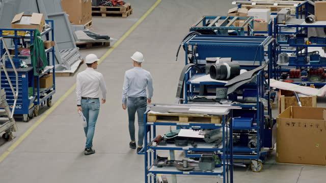 slo mo zwei ingenieure gehen durch die produktionsanlage - industriegerät stock-videos und b-roll-filmmaterial