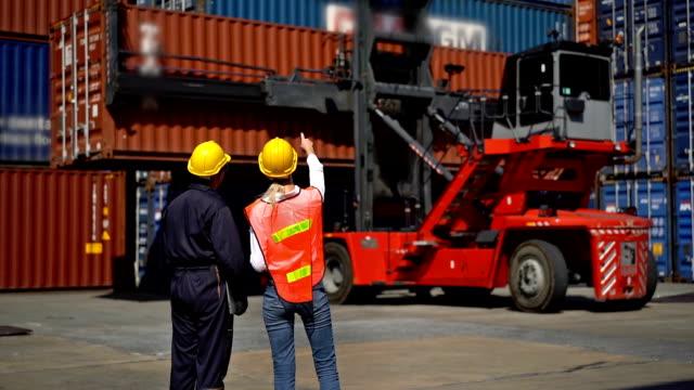 zwei ingenieure arbeiten mit gabelstapler in shipping yard - dockarbeiter stock-videos und b-roll-filmmaterial
