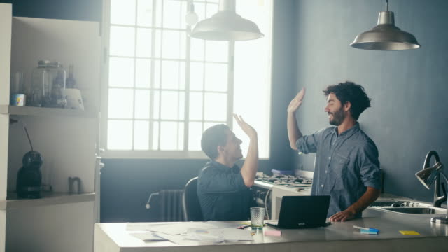 vídeos de stock e filmes b-roll de two enthusiastic male employees high-fiving at the office (slow motion) - support