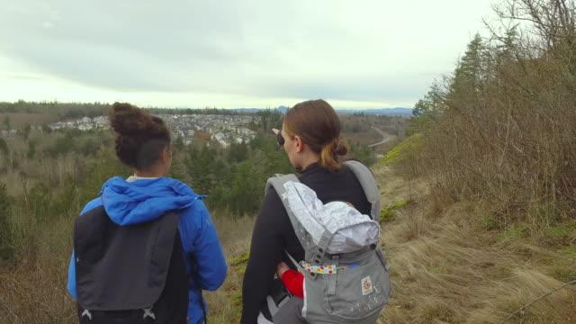 stockvideo's en b-roll-footage met twee etnische vrouwen wandelen met baby - fatcamera