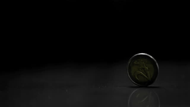two euro coin spinning on black background - european union coin stock videos & royalty-free footage