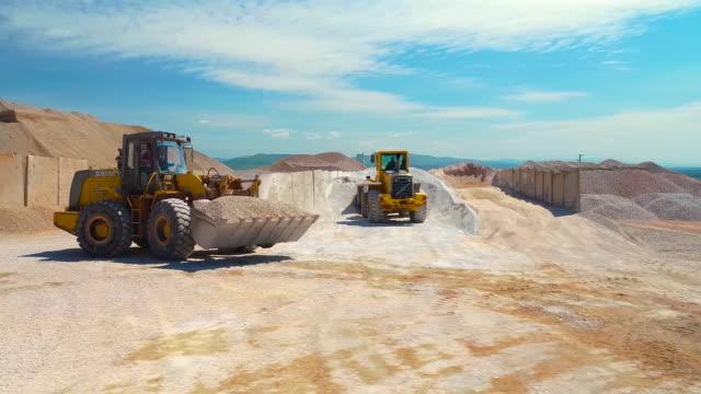 vídeos y material grabado en eventos de stock de dos excavadoras que trabajan en la fábrica de asfalto, vista aérea - maquinaria de construcción