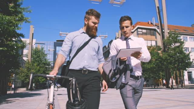 SLO MO deux cadres à l'aide de tablette numérique tout en marchant dans la ville