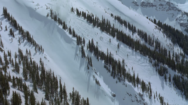 Two explosions start an avalanche down a steep mountain slope.