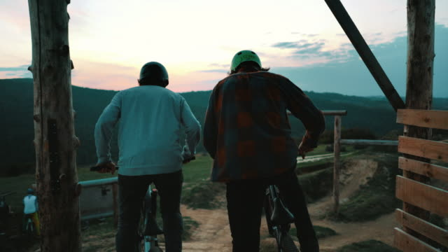 Two extreme sportsmen on mountain bicycles fist bumping and starting a race on extreme terrain.