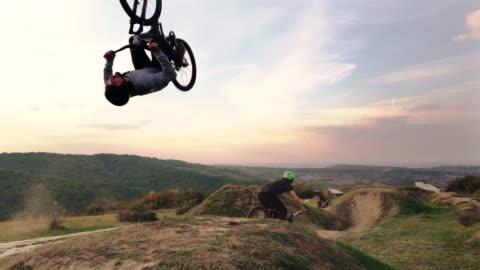 vídeos y material grabado en eventos de stock de dos deportistas extremos en bicicletas de montaña, practicando en terreno extremo. - deporte de riesgo