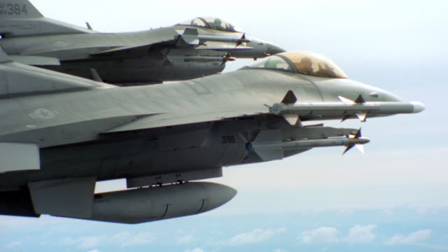 two f-16 jet fighters fly side by side, high above land and patchy clouds. - g force stock videos & royalty-free footage