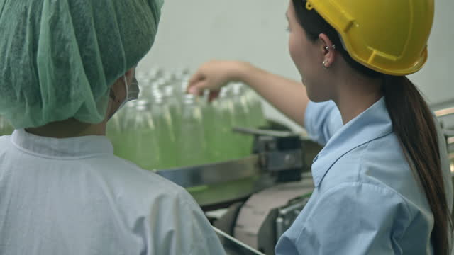 two factory worker checking the bottles in row on conveyor belt - quality control stock videos & royalty-free footage