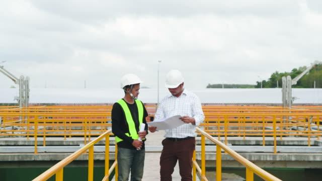 2人の工場労働者が青写真で歩いて議論した。産業背景 - 助言点の映像素材/bロール