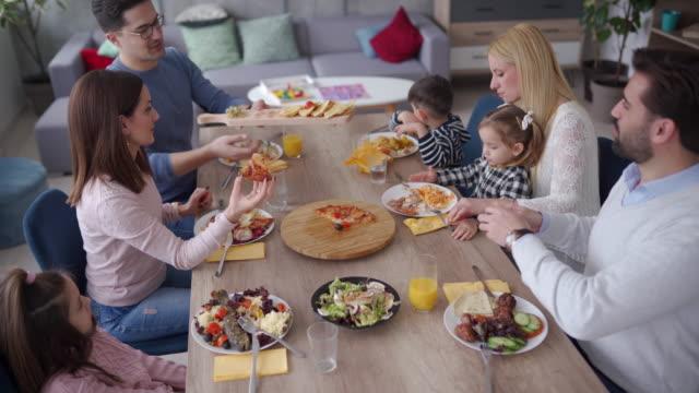 zwei familien beim gemeinsamen mittagessen zu hause - junge familie stock-videos und b-roll-filmmaterial