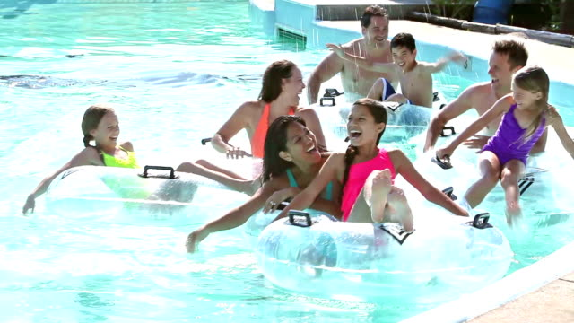 two families on lazy river at water park - laziness stock videos & royalty-free footage
