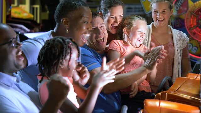 vídeos de stock e filmes b-roll de two families playing an arcade game - 14 15 anos