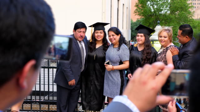 ms two families posing for pictures with graduating daughters during meal on restaurant deck - mortarboard stock videos and b-roll footage