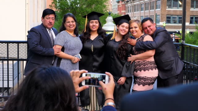 ms two families posing for pictures with graduating daughters during celebration meal on restaurant deck - mortarboard stock videos and b-roll footage