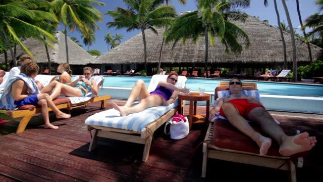 vídeos de stock e filmes b-roll de two families relaxing together at tropical pool - família com quatro filhos