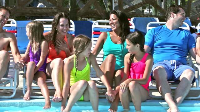 会話プールのサンラウン ジャーで座っている 2 つの家族