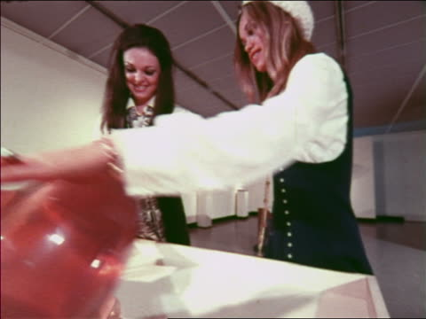 1970 two fashion models playing with giant top in art museum / atlanta / travelogue - toy stock videos and b-roll footage