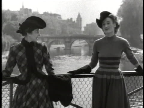 vidéos et rushes de two fashion models stand on a bridge over the seine river in paris, france. - 1947