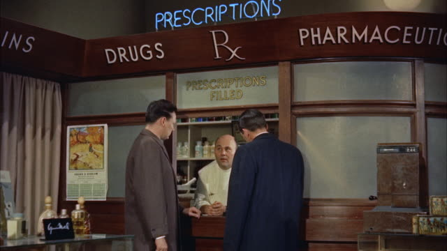 vídeos de stock, filmes e b-roll de ms two fbi agents  questioning to drug prescription clerk - 1950 1959