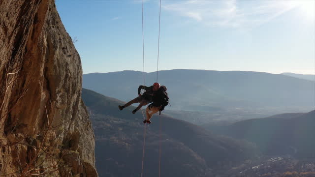 two fearless rock climbers hanging on a rope - safety harness stock videos & royalty-free footage