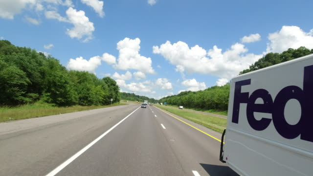 two fedex trucks on the highway coming from opposite directions in america amid the 2020 global coronavirus pandemic - pursuit concept stock videos & royalty-free footage