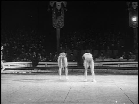 stockvideo's en b-roll-footage met b/w 1955 two female acrobats in costumes doing handstands + flipping over in synch - acrobaat