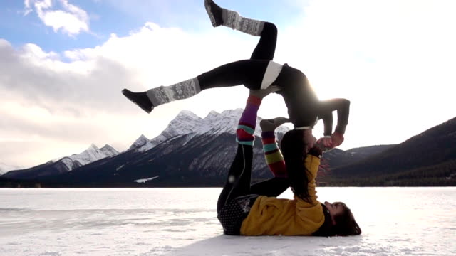 Two female acrobats perform maneuvers in snow