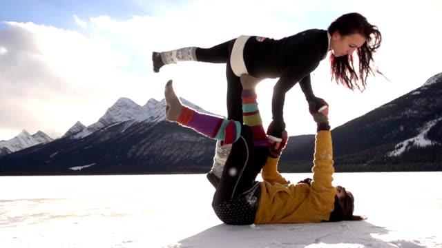 stockvideo's en b-roll-footage met two female acrobats perform maneuvers in snow - acrobaat