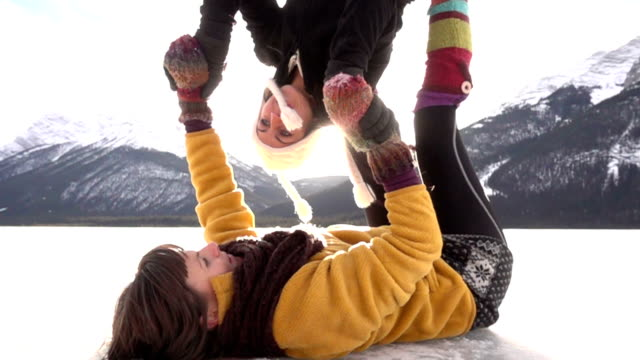 two female acrobats perform maneuvers in snow - mitten stock videos and b-roll footage