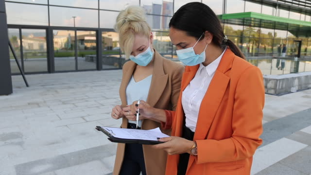 two female architects with protective face masks looking at blueprint on clipboard in front of office building - clipboard stock videos & royalty-free footage