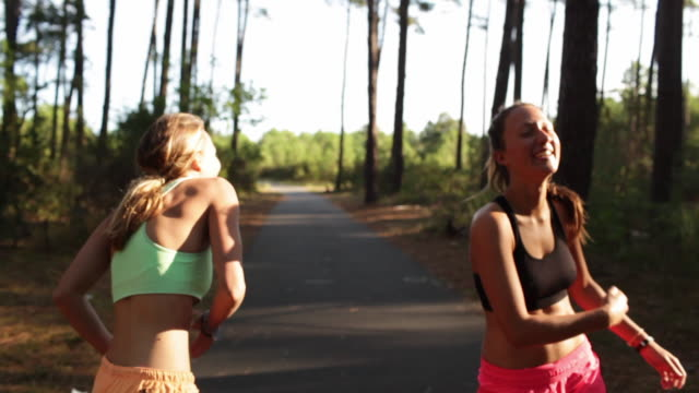 Two female athletes giving each other high fives in the forest by the beach in the South of France