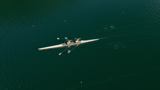 aerial two female athletes gliding across a lake in a double scull - rowing stock videos & royalty-free footage