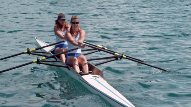 two female athletes in a double scull moving across the lake in sunshine - rowing stock videos & royalty-free footage