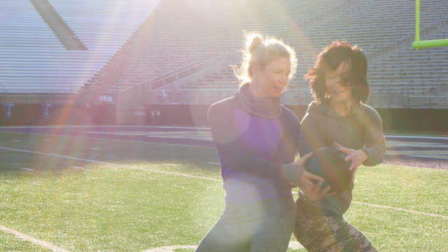 MS Two female athletes passing medicine ball back and forth while training on football field in empty stadium