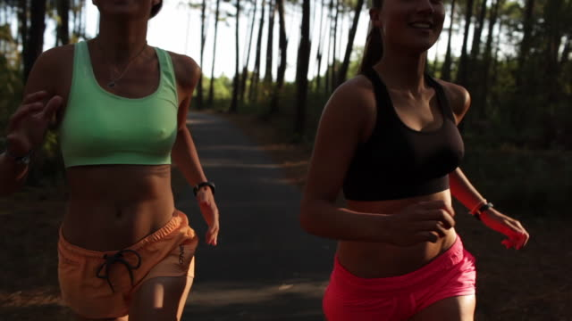 two female athletes running in the forest by the beach in the south of france - sportbehå bildbanksvideor och videomaterial från bakom kulisserna