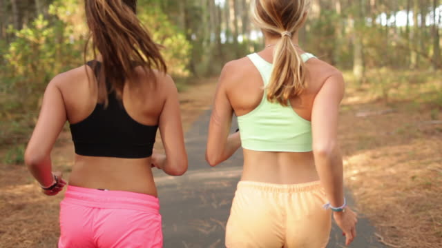 vídeos de stock, filmes e b-roll de two female athletes running in the forest in the south of france. - short curto