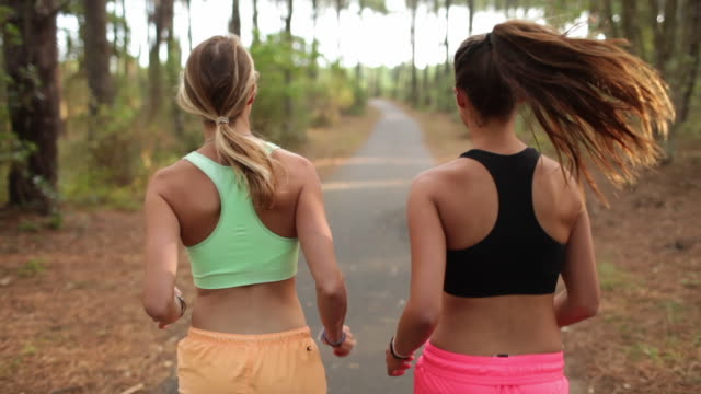Two female athletes running in the forest in the south of France.