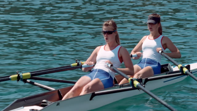 two female athletes sculling across a lake - sun visor stock videos and b-roll footage
