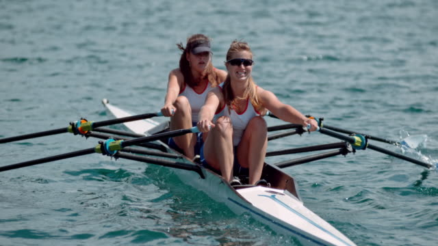 slo mo two female athletes sculling across the lake in sunshine - rowing stock videos & royalty-free footage