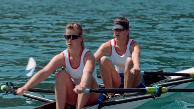 two female athletes sculling across the water in sunshine - rowing stock videos & royalty-free footage