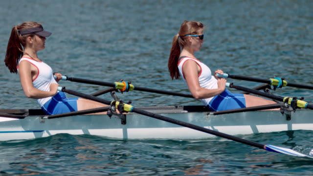 slo mo ts two female athletes sculling on a sunny lake - rowing stock videos & royalty-free footage