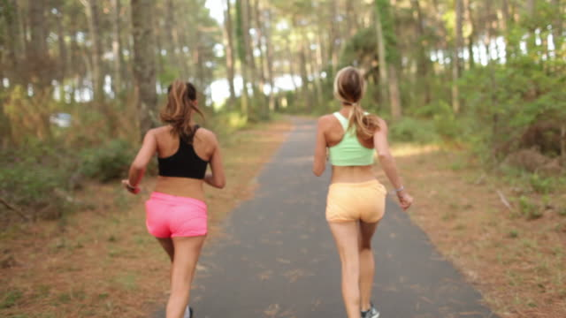 vídeos de stock e filmes b-roll de two female athletes sprinting and laughing in the forest in the south of france. - mulheres jovens