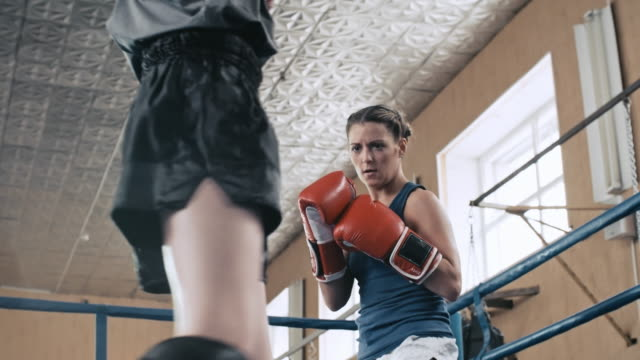 Two female boxers attacking each other in the ring