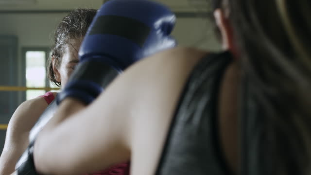 Two female boxers boxing in the boxing ring