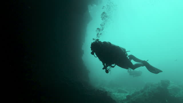 two female buddies scuba diving through underwater cave - thailand stock videos & royalty-free footage