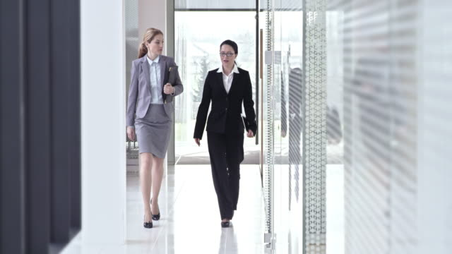 SLO MO Two female business coworkers walking down hallway and talking
